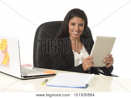 corporate portrait of young attractive hispanic businesswoman sitting at office computer desk smiling happy using digital tablet in successful female worker and business success concept