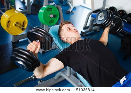 Exercising with dumbells at gym. Man in black t-shirt.