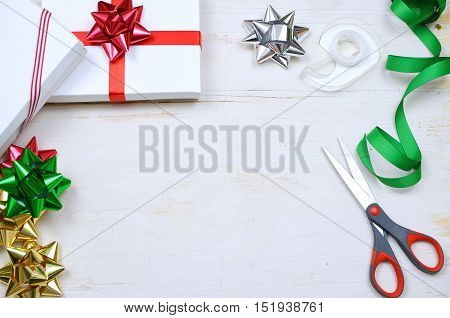 Christmas gifts colorful ribbons and bows with scissors and tape form a border around a rustic white washed wooden table top. Overhead perspective. Copy space