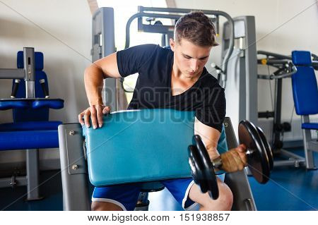 Young man biceps workout on a smitbench.