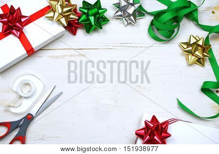Christmas gifts colorful ribbons and bows with scissors and tape form a border around a rustic white washed wooden table top. Overhead perspective. Christmas greeting added