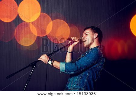 Young Man Singing with Microphone. Singer Performance. Concert and Music Concept. Toned Photo with Bokeh.