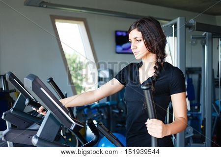 Running brunette in black t-shirt at gym.