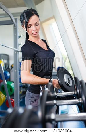 Caucasian girl with dumbbells in a gym.