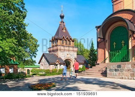 KUREMAE, IDA-VIRUMAA COUNTY, ESTONIA - AUGUST 21, 2016: People near Dormition Cathedral and The Saint Gate with Belfry. Puhtitsa Dormition Convent  The Estonian Orthodox Church of Moscow Patriarchate