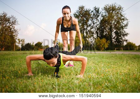 Two girls doing push-ups . Outdoor hard workout.