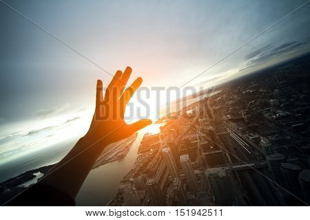 hand closing from sun light on roof top of city; tourist on top of tower;