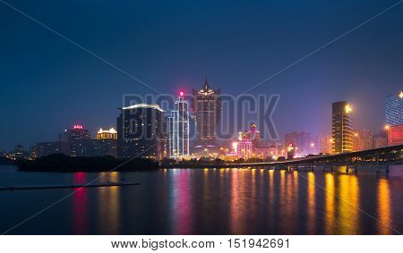 Skyline of Macau city at Nam Van Lake, China. The city maintains the world's highest gambling revenue with over 20 million tourists annually.