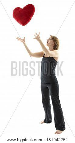 Woman throws a heart pillow in the air