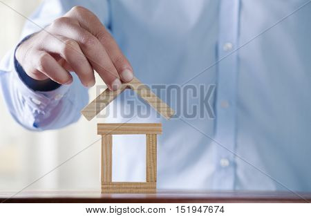 Man's hand holding wooden block. Building a house.Real Estate business