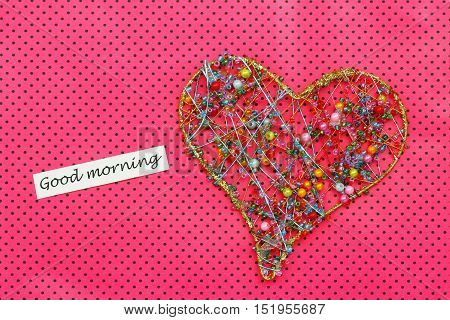 Good morning card with heart made of colorful beads on dotty pink surface