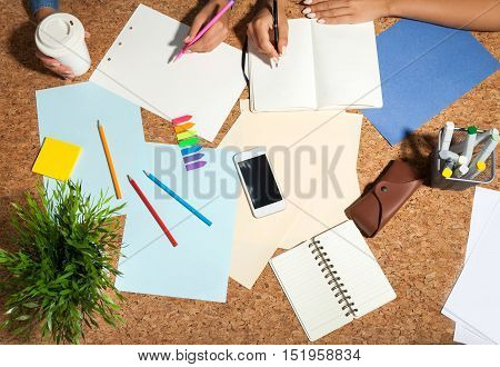 Top view of two women writing and drawing at one table and hindering each other because one is left handed and the second is right handed and they sit in a wrong way. Concept of strategy.