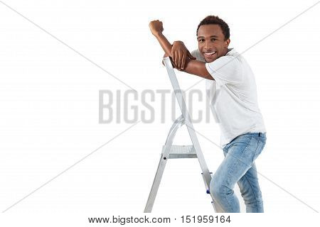 Smiling African American handyman in blue jeans is standing on stepladder and looking to the camera. Concept of handicraft. Mock up