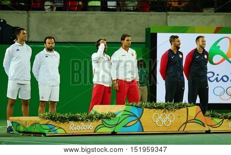 RIO DE JANEIRO, BRAZIL - AUGUST 12, 2016: Tean Romania (L) , team Spain Mark Lopez and Rafael Nadal of Spain and Team USA during medal ceremony after  men's doubles final of the Rio 2016 Olympic Games