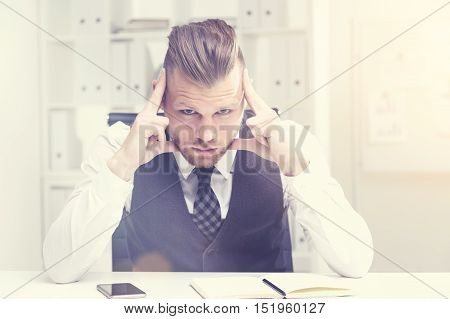 Serious businessman is sitting in his office and thinking hard about the current events in the company looking for solution. Concept of thinking. Toned image