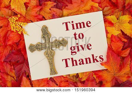 An inspirational message Some fall leaves with a blank beige greeting card with a cross with text Time to give Thanks