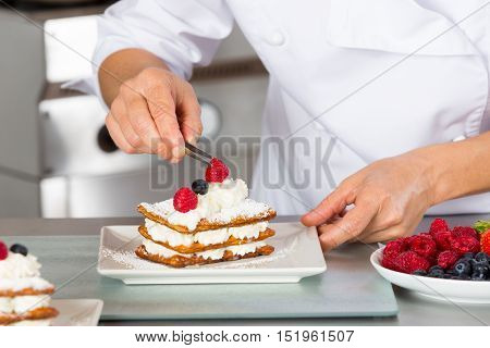 Pastry chef decorating with berries pie pastry