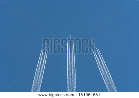Three planes flying at high altitude. Contrails against a dark blue sky.