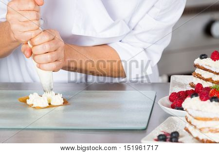 Cream filling pastry chef on a puff pastry