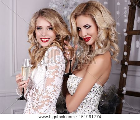 fashion studio photo of beautiful girls with blond hair and charming smilesposing beside Christmas tree and presents with glass of champagne