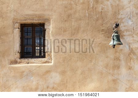 The old prison wall window with iron bars and alarm bell.