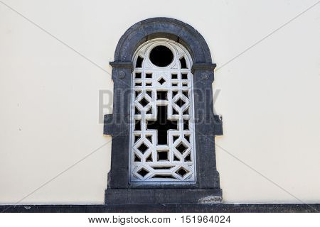 An old prison window with a stone wall grille with a cross symbol of faith.