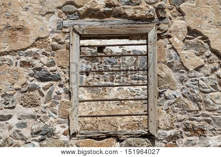 The ruins, the ruins of the destroyed castle fortress wall with a window with iron bars. The wall of the old prison window with bars on the escape of criminals