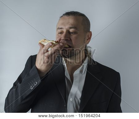 a man in a jacket eating a slice of pizza