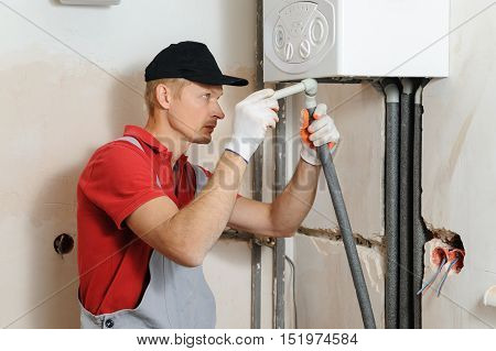 Installation of home heating. Worker attaches the pipe to the gas boiler.