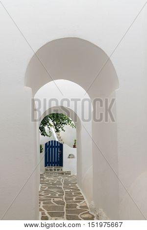 Arched doorways leading to a blue door. Traditional architecture of local villages at Paros island in Greece.