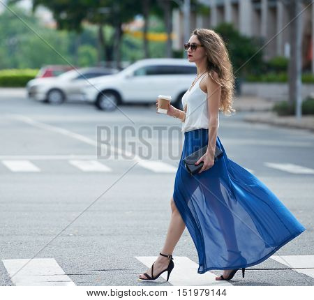 Side view of woman in long flattering skirt crossing road