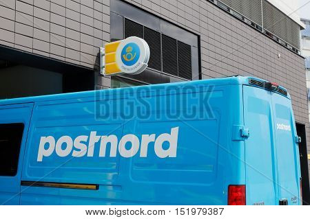 Solna, Sweden - June 15 2016: A blue van marked with Postnord the Swedish postal service parket outside the post office at the street Englundavagen in Solna Buissness park.