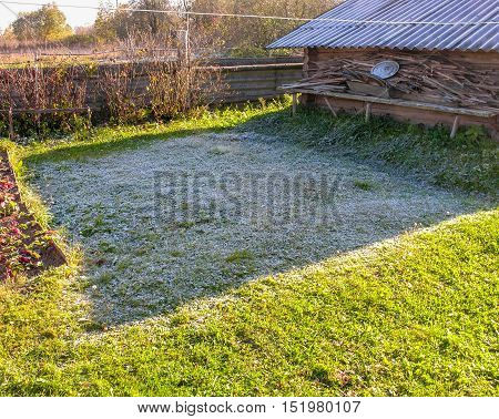 Frost on the grass after the first night frost does not melt for a long time in the shadow of the shed