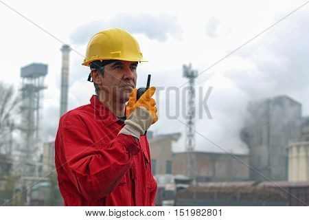 Industrial worker in sugar refinery. A portrait of a worker in red overalls and yellow helmet.