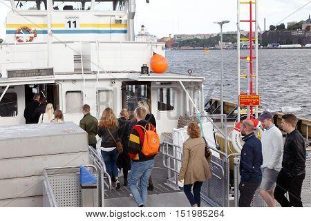 Stockholm, Sweden - June 9, 2016: People boarding the public transport Djurgarden ferry at the Slussen stop.