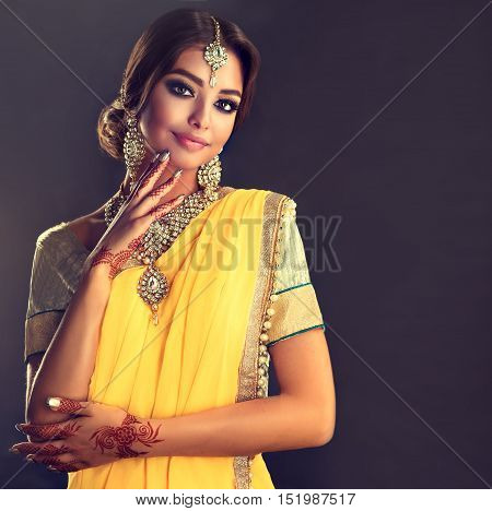 Portrait of beautiful indian girl . Young hindu woman model  with tatoo mehndi  and kundan jewelry . Traditional Indian costume  yellow saree