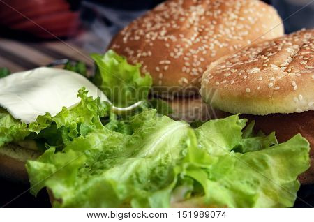 Lettuce and a slice of cheese on a bun with sesame seeds. Cooking burger concept
