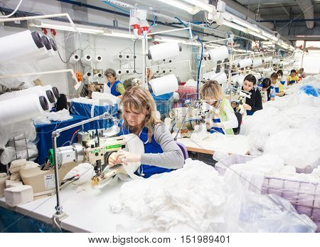 GRODNO BELARUS - DECEMBER 13 2013: Seamstress in textile factory sewing with a industrial sewing machine .
