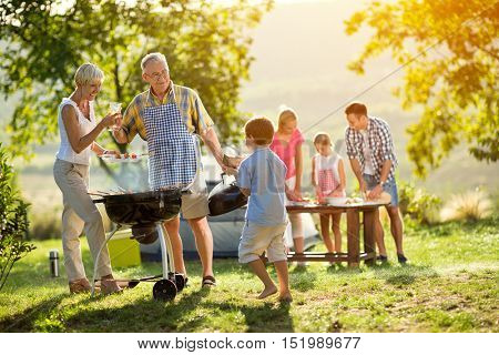 grandson helps grandparents to make a barbecue for family