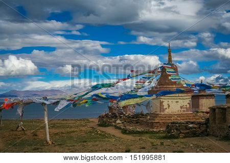 Small old Tibetan monastery and praying mills on a hill above holy Lake Manasarovar, Tibet