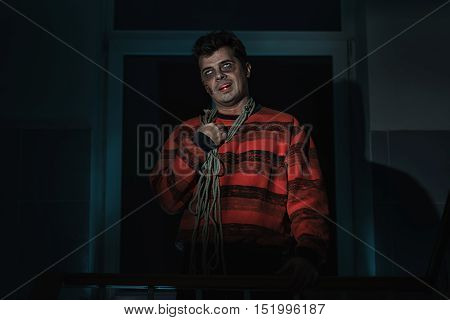 Scary man killer with a knife in the room.