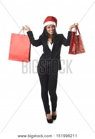young happy beautiful latin woman with christmas santa hat holding sale shopping bags excited and cheerful isolated on white background in shopaholic and xmas gift concept