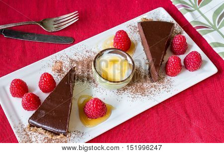 Slice of chocolate torte with raspberries on a white plate and a red placemat.