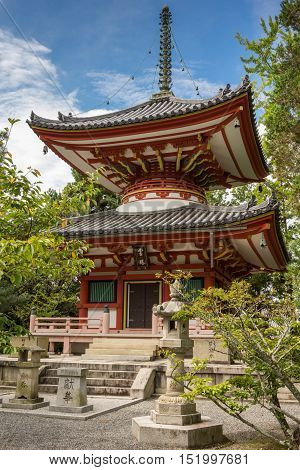 Kyoto Japan - September 16 2016: The wooden monumental vermilion pagoda at Chion-in Buddhist Temple stands under blue skies in the green park.