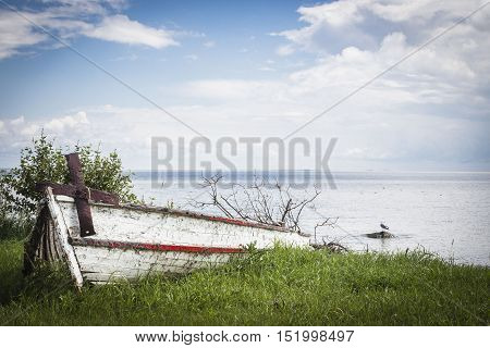 horizontal image of a very old broken canoe with cracked white paint and an old rusted anchor hanging over the side next to a big lake in the summer time.