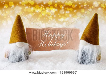 Christmas Greeting Card With Two Golden Gnomes. Sparkling Bokeh And Noble Background With Snow. English Text Happy Holidays