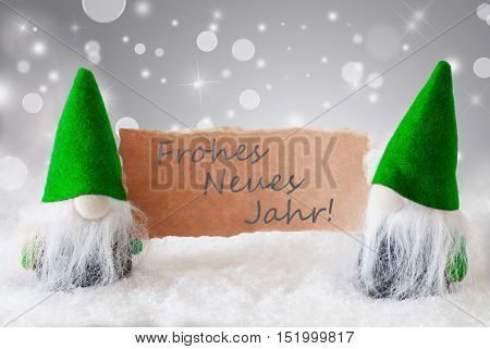 Christmas Greeting Card With Two Green Gnomes. Sparkling Bokeh And Noble Silver Background With Snow. German Text Frohes Neues Jahr Means Happy New Year