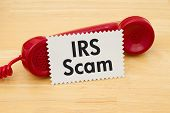 Getting a call that is an IRS Scam A retro red phone with note card on a desk with text IRS Scam poster