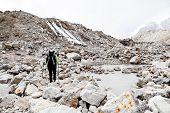 Woman hiker trekking with big backpack in Himalaya Mountains on Rocky Glacier Trail. Girl on hiking trail in high mountains travel and expedition in inspirational mountain landscapebeautiful views. poster