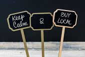 Keep Calm and Buy Local message written with chalk on mini blackboard labels defocused chalkboard and wooden table in background. Fun and humor concept poster